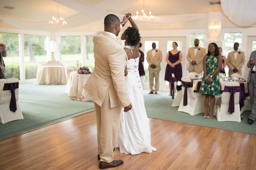 Groom twirls his bride during their first dance at their wedding reception