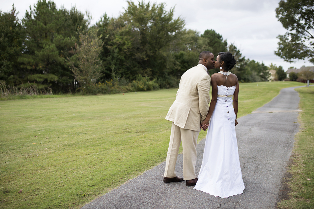 Bride and groom kiss on a path in a golf course in Chesapeake, Virginia
