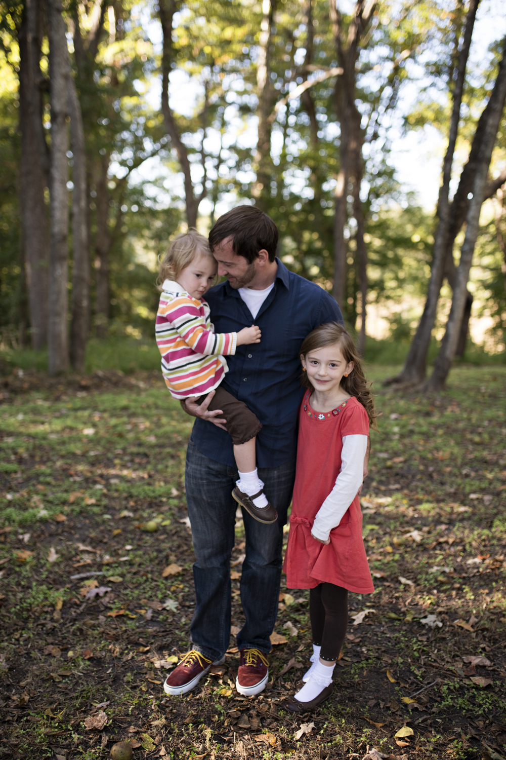 A dad with his daughters in the fall