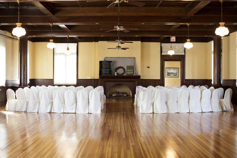 Indoor wedding ceremony with hardwood floors and fireplace