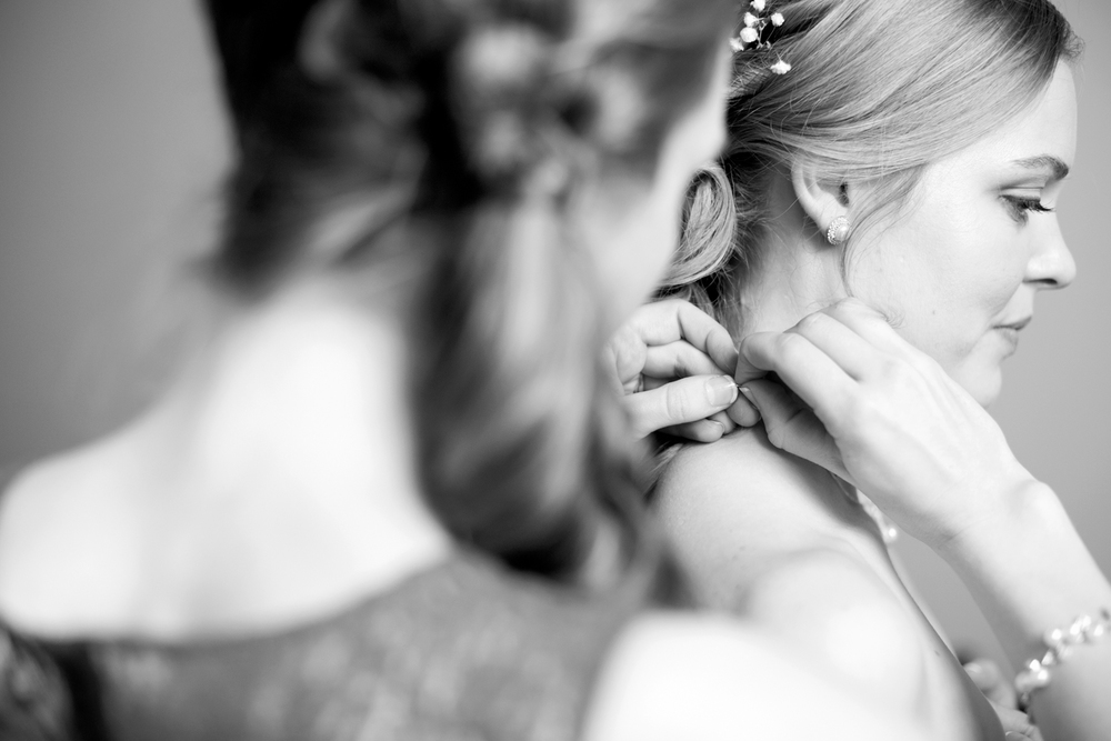 Maid of honor helping bride put on necklace (black and white)