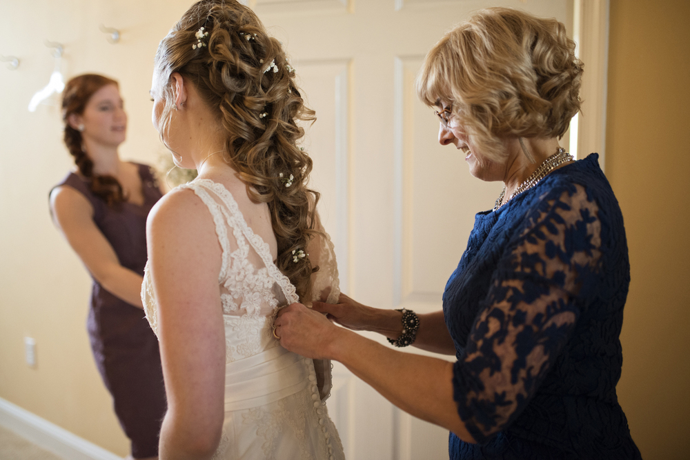 Mother of bride helping put on her lace dress