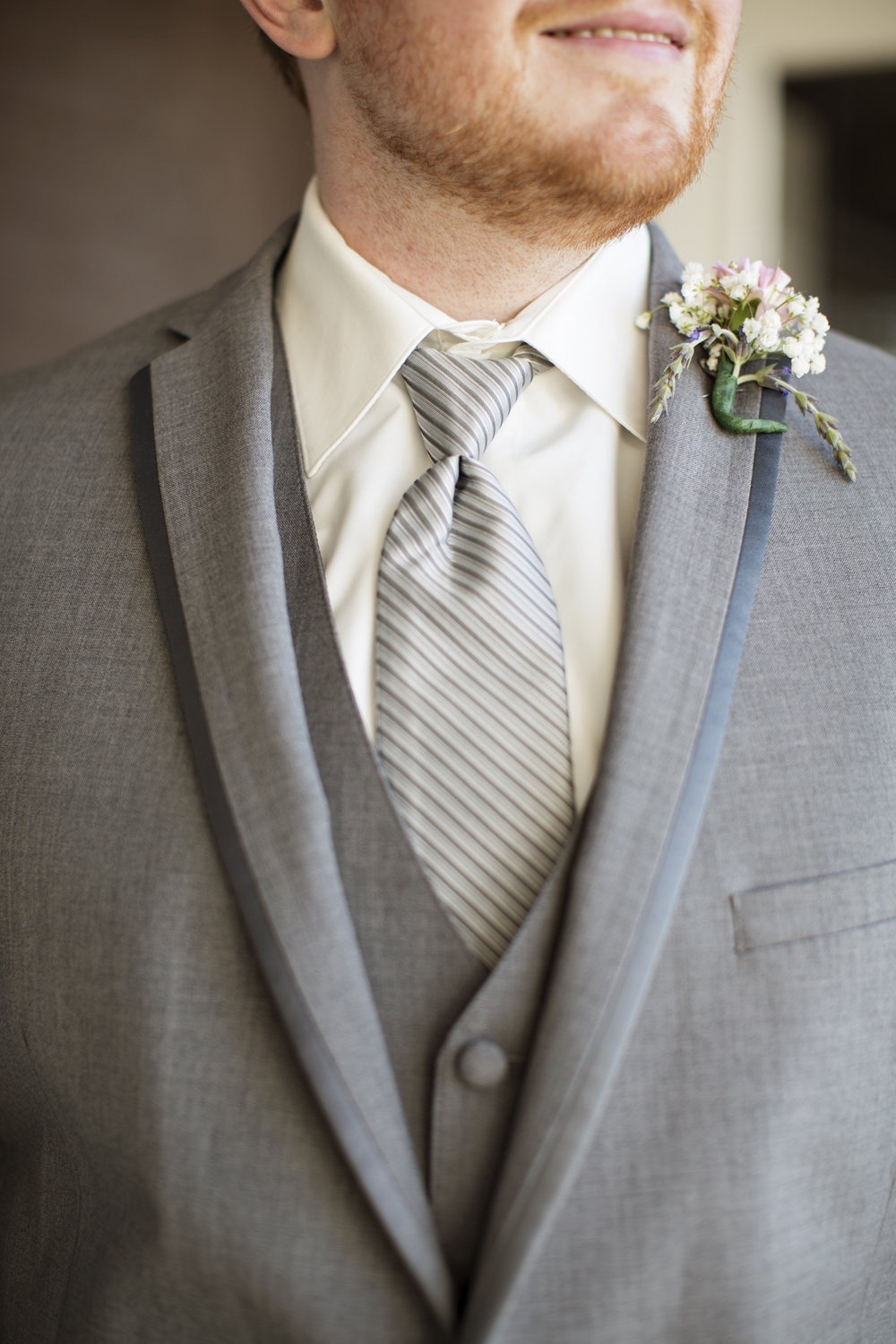 Groom in gray tux with baby's breath boutonniere