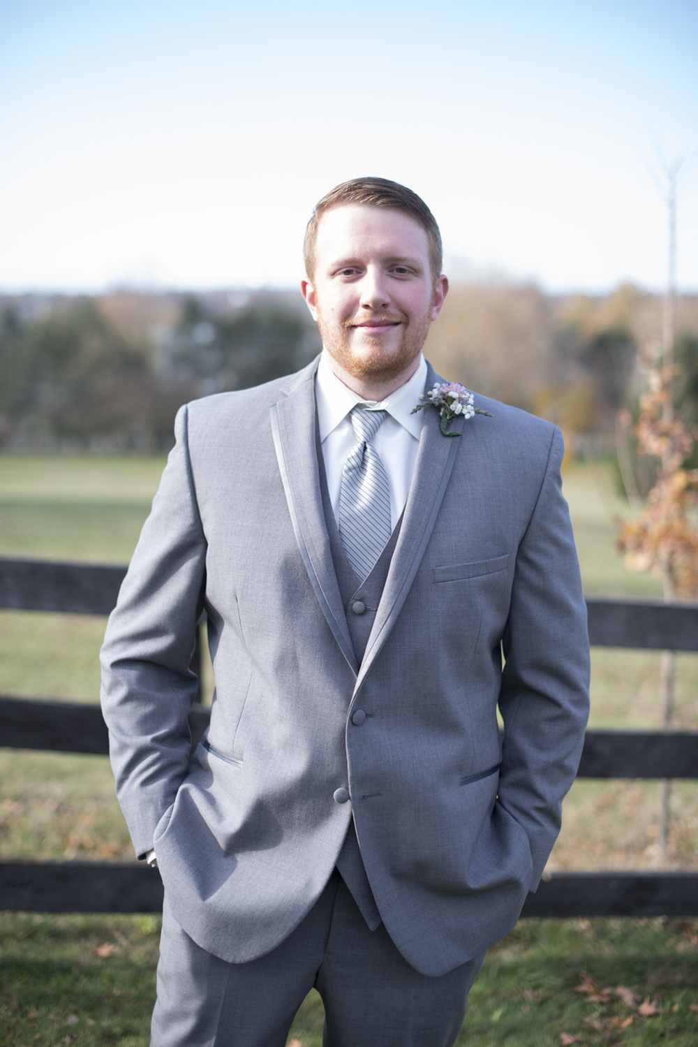 Groom's portrait in gray tuxedo outdoors