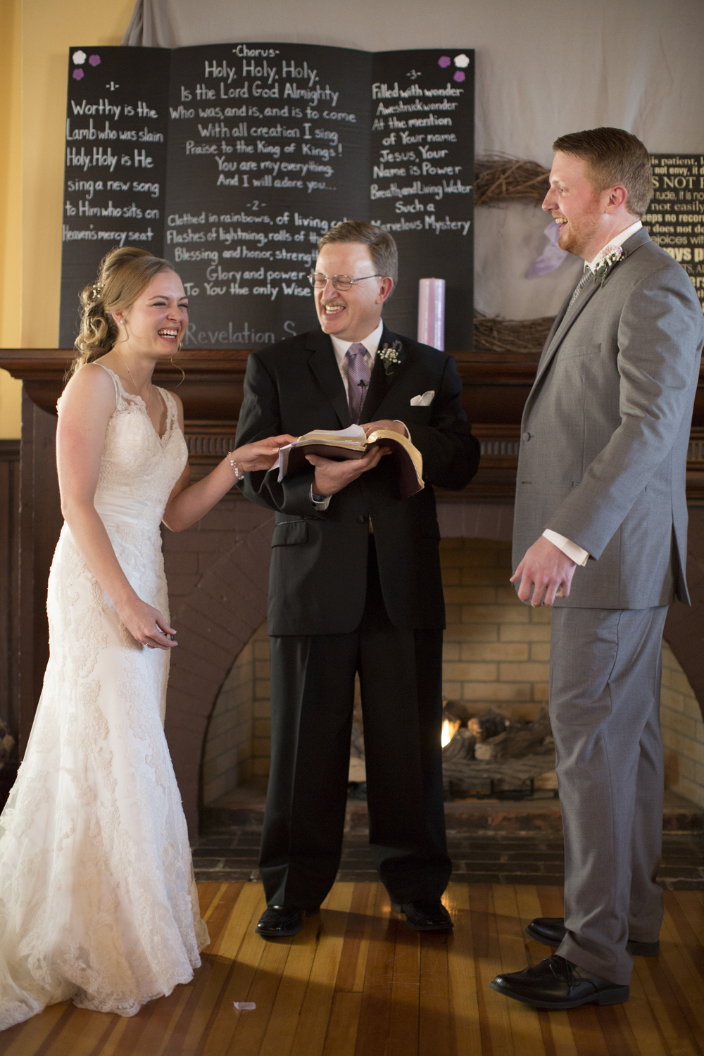 Bride and groom laugh with officiant on their wedding day