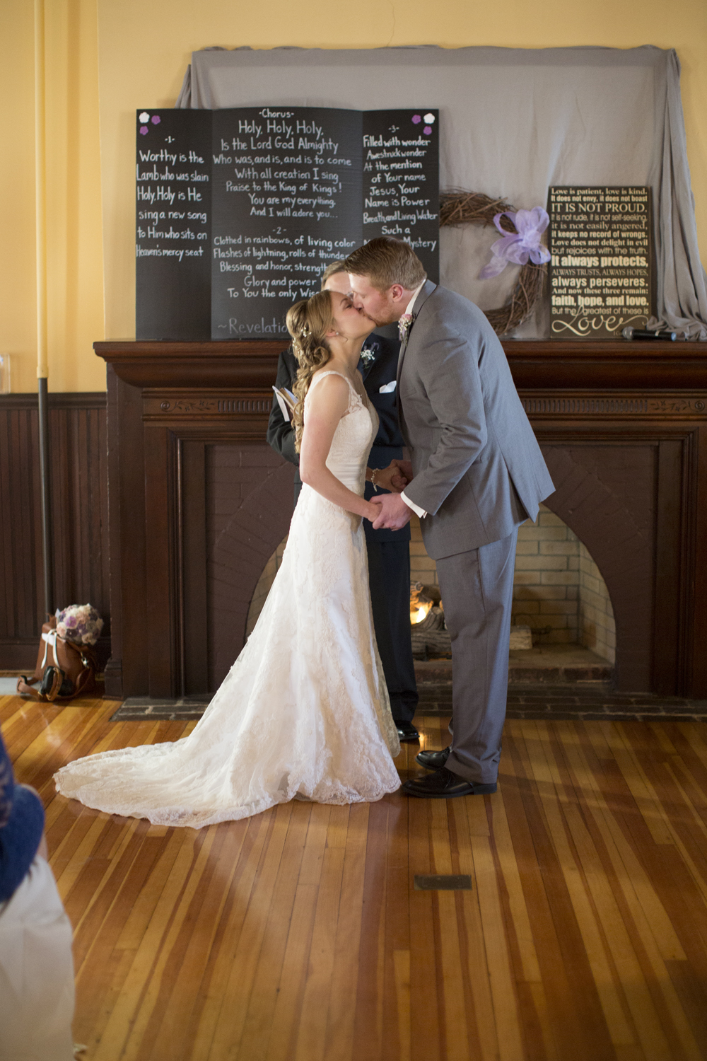 Bride and groom's first kiss at the altar of their indoor wedding ceremony in front of a fireplace