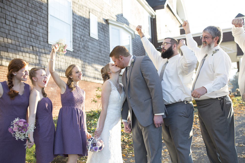 Bridal party cheers while the bride and groom kiss