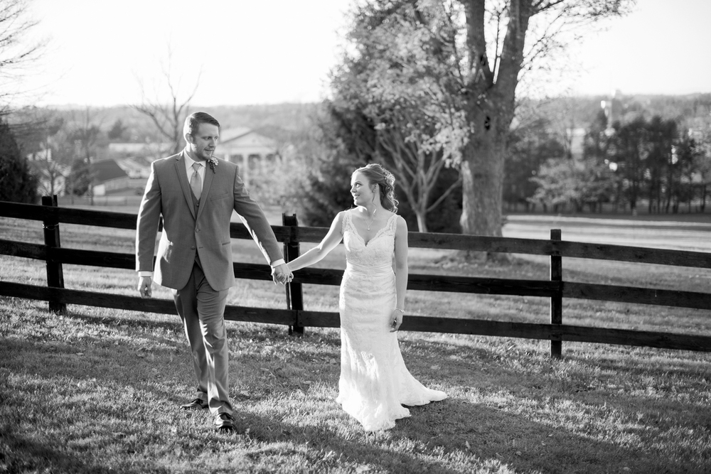 Bride and groom walk together at sunset on a hill (black and white)