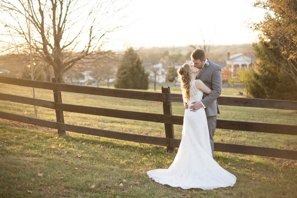 Bride and groom kiss at sunset against a fence in the fall in Virginia