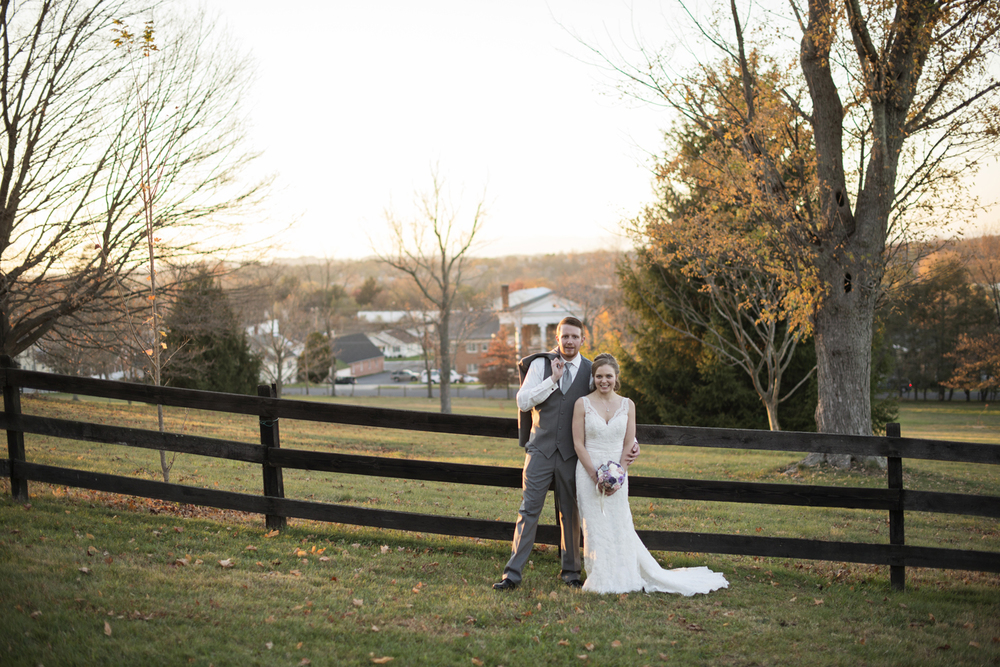Bride and groom stand by a fence overlooking the city