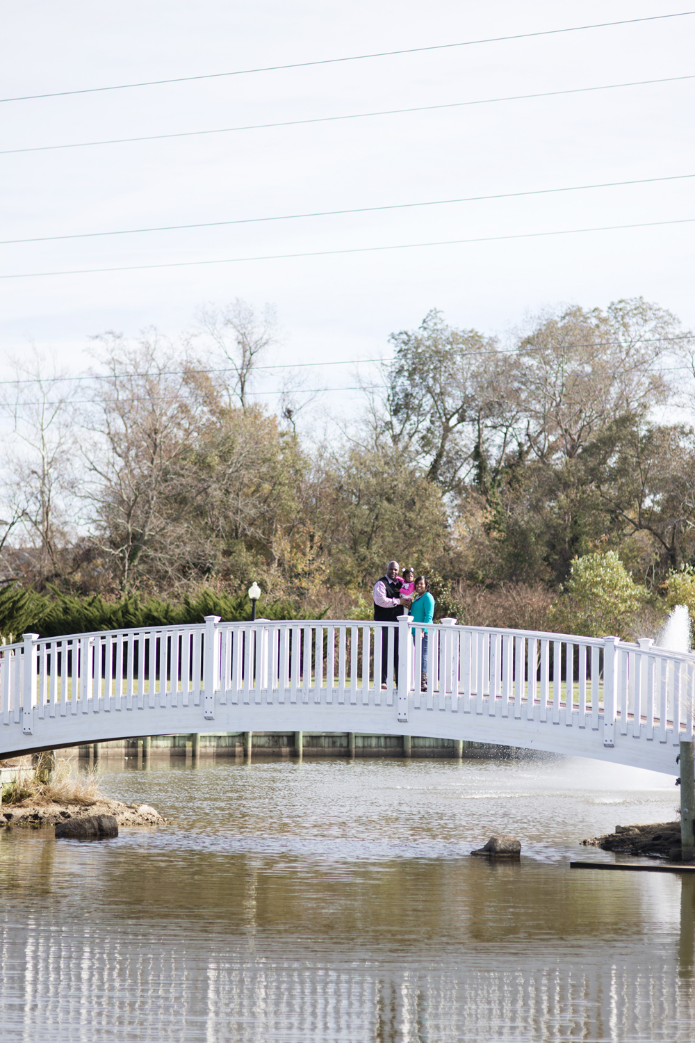 Family of three poses on a bridge for pictures