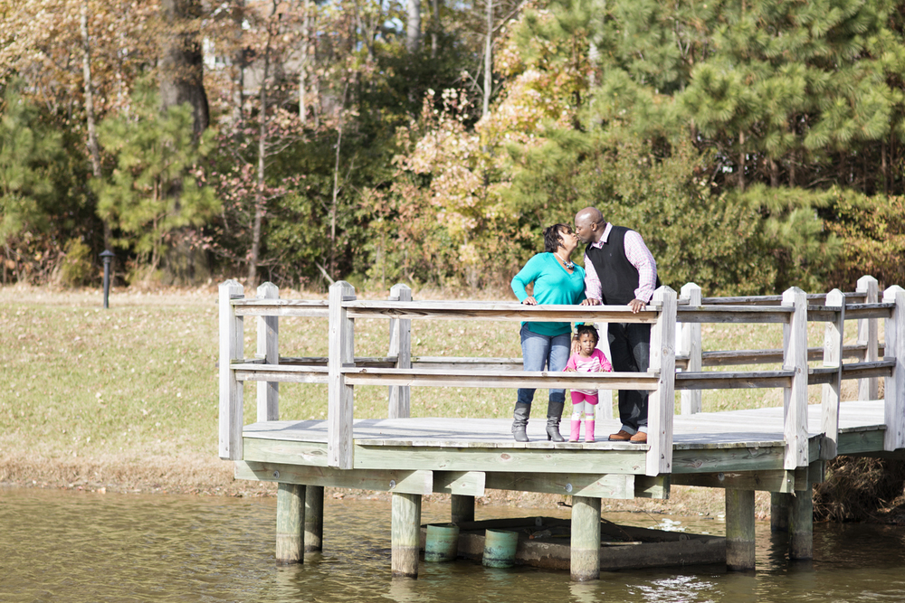 Family portraits with mom and dad kissing on a dock