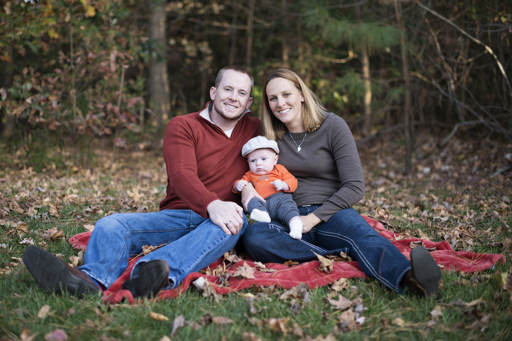 Fall family pictures with leaves and a red blanket