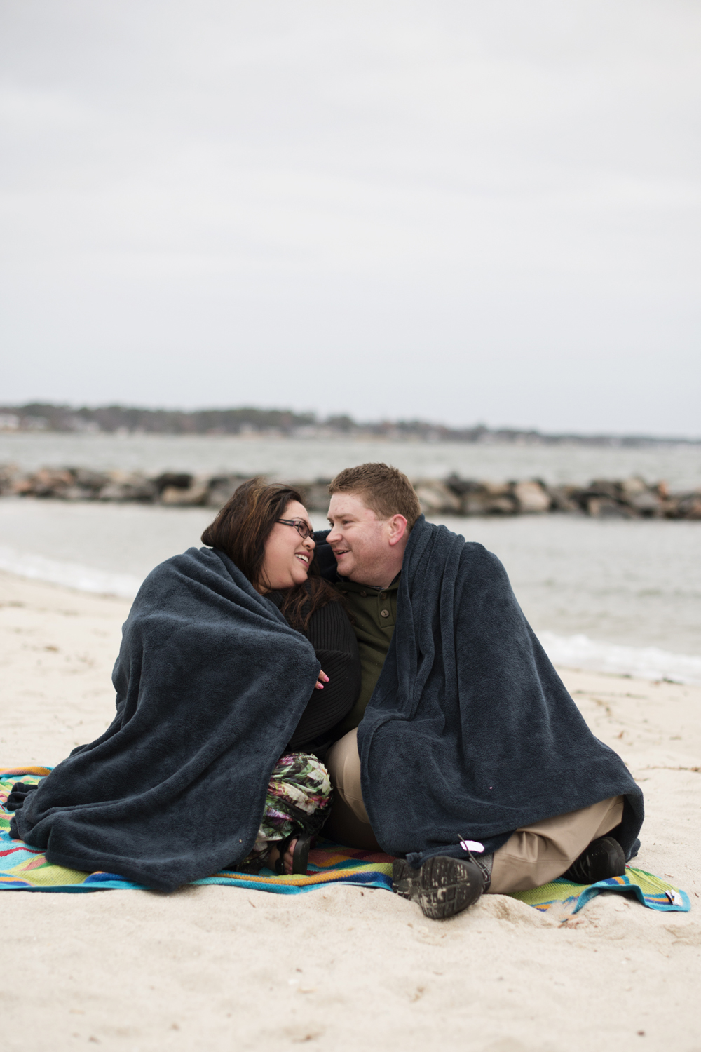 Winter beach engagement session posing ideas with a blanket