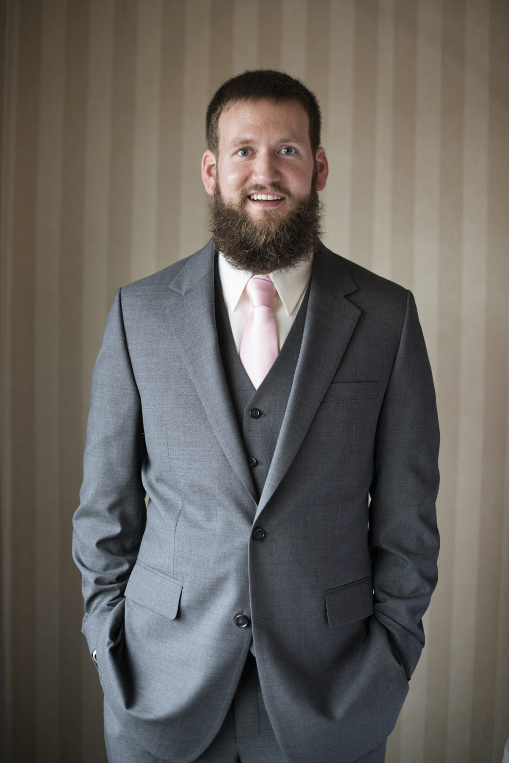 Groom wearing gray and pink for his December wedding