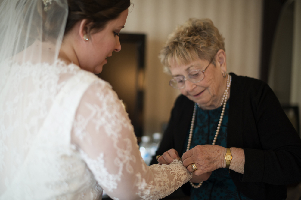 Bride's grandmother putting on jewelry