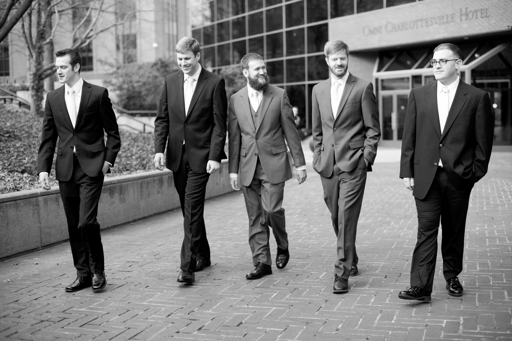 Black and white groomsmen pictures walking through the street