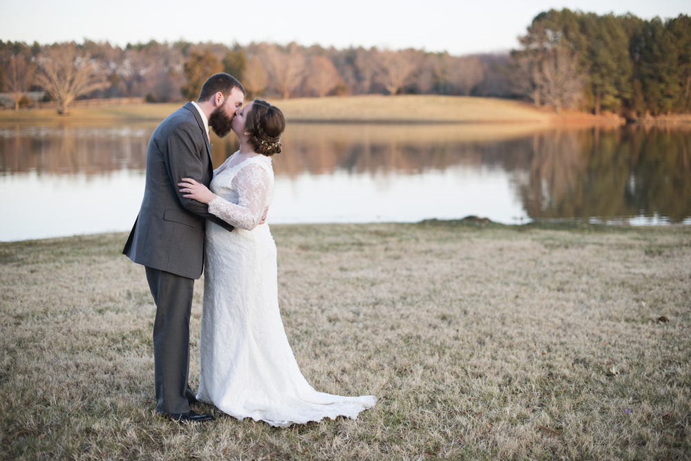 Bride and groom portraits by a lake at sunset