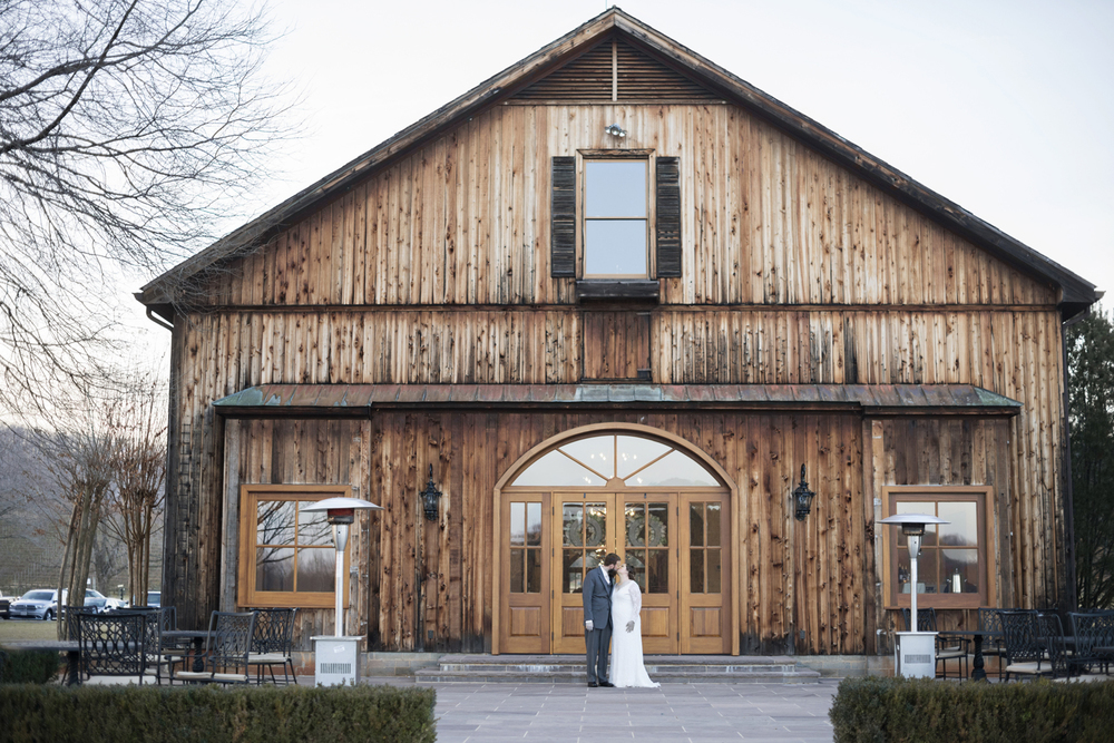 Bride and groom portraits in front of a barn at sunset