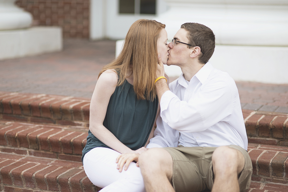 Kissing on the steps | Engagement session | Emerald green, white, and khaki
