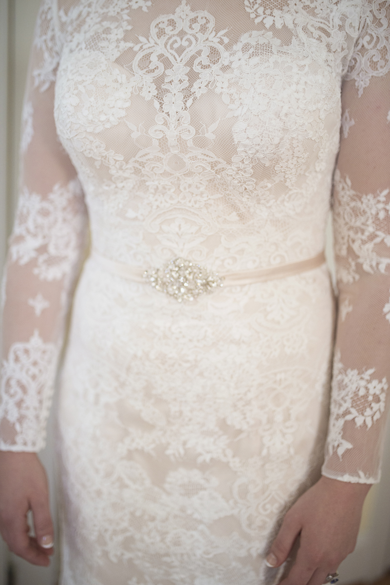 All lace long sleeved cream wedding dress with sequin belt