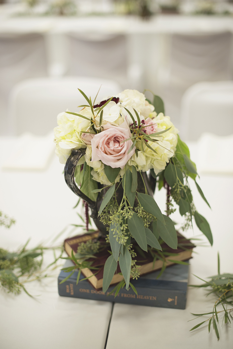 Classic wedding reception centerpieces with blush roses, white flowers, and eucalyptus on vintage books