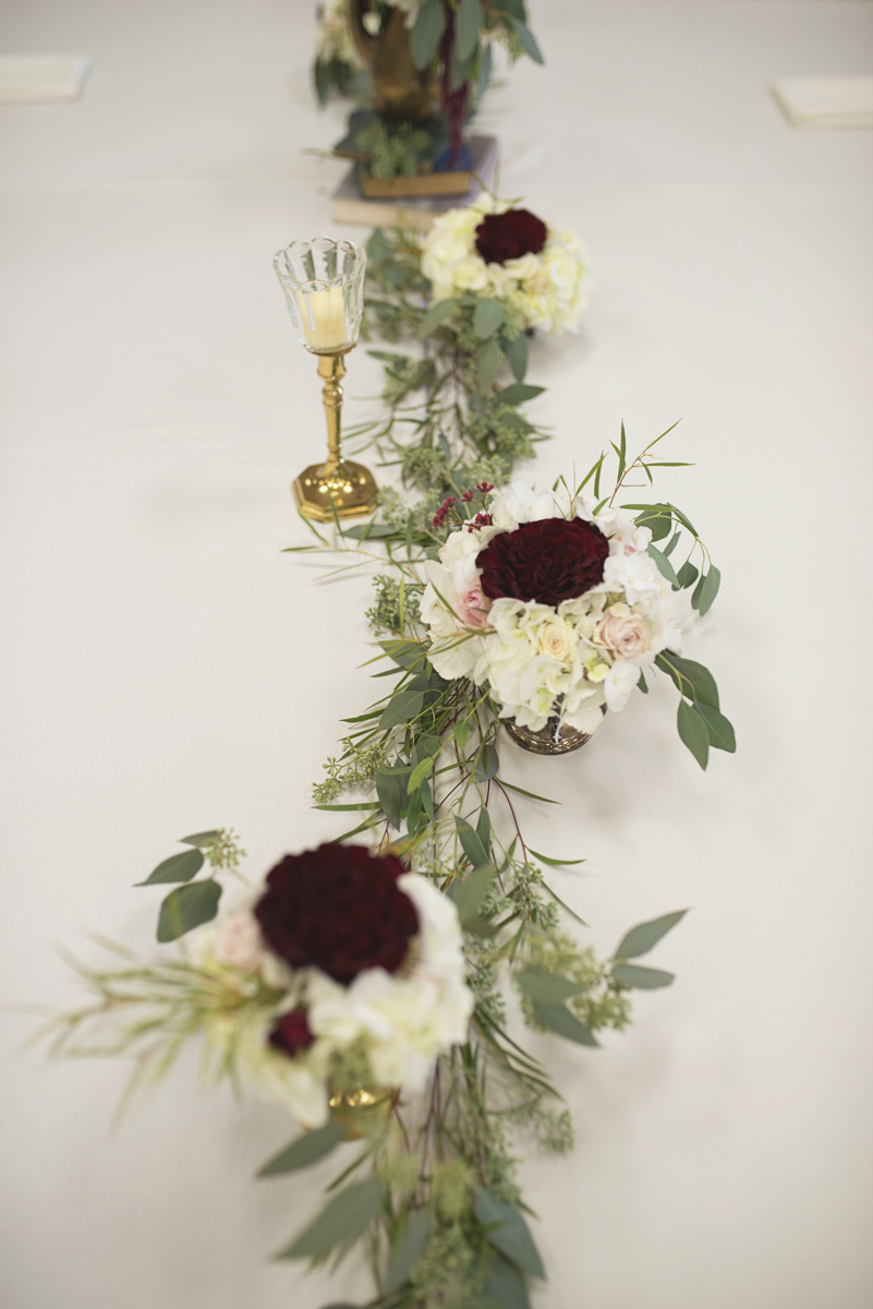 Classic wedding reception centerpieces with blush roses, white and crimson flowers, and eucalyptus