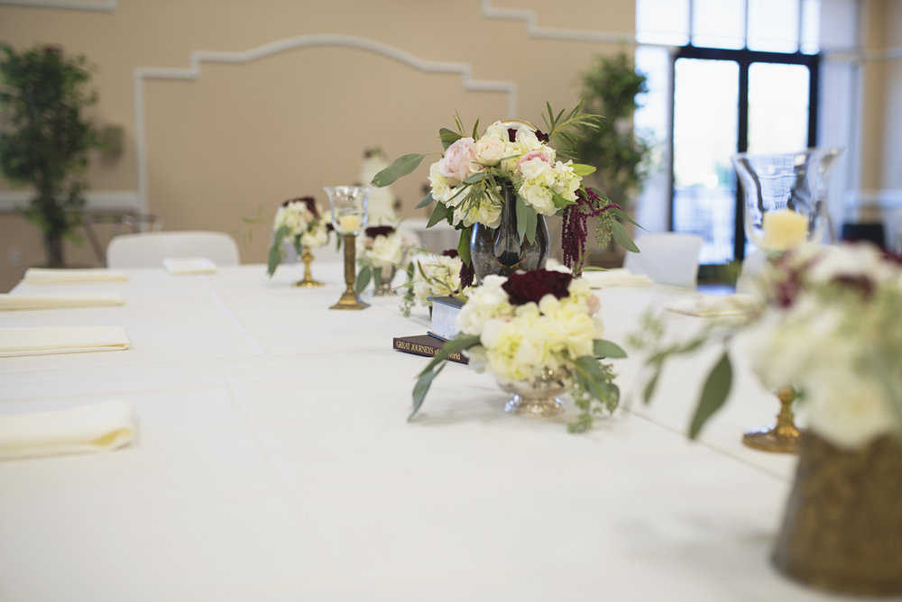 Classic wedding reception centerpieces with blush roses, white flowers, and eucalyptus in vintage pitchers