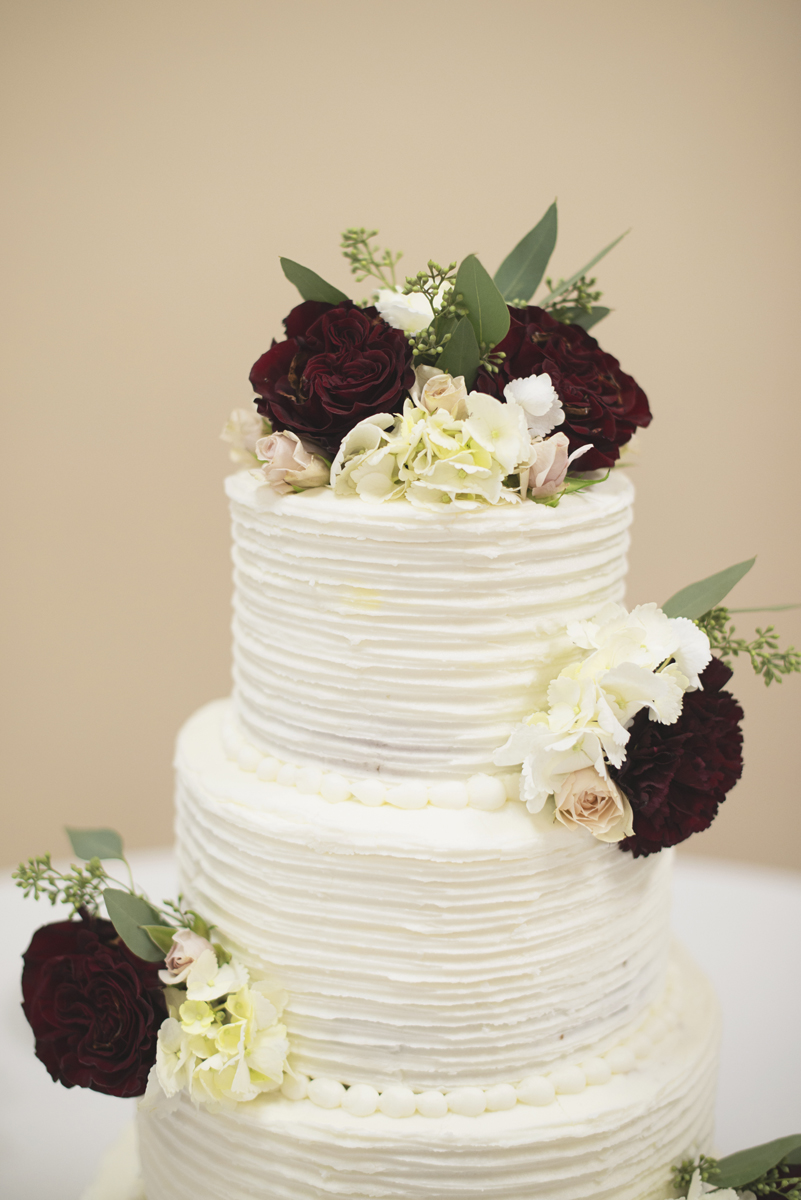 Simple white wedding cake with crimson, white, and blush flowers and eucalyptus leaves