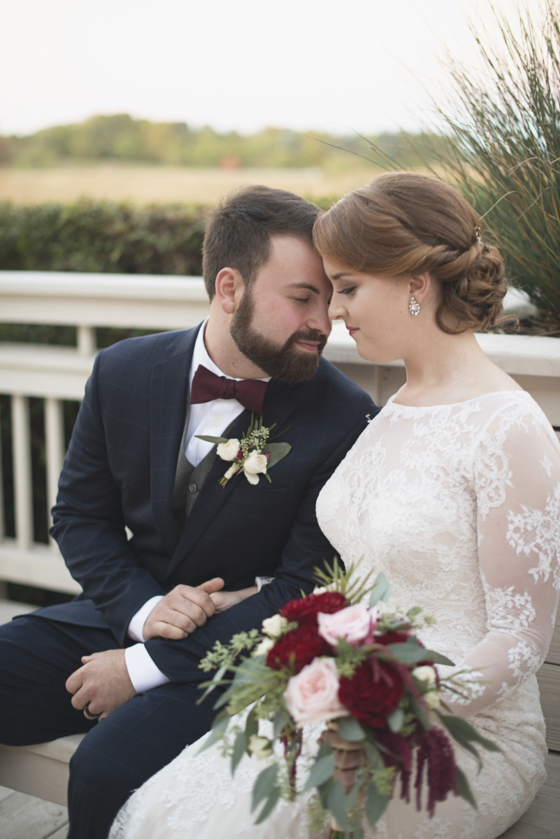 Bride and groom portraits with crimson and blush bridal bouquet at sunset