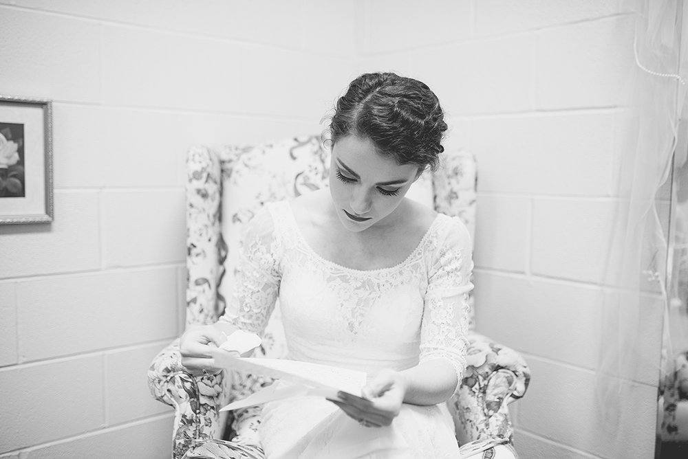 Downtown Nashville Winter Wedding | Crimson and Black Wedding | Bride reading groom's letter