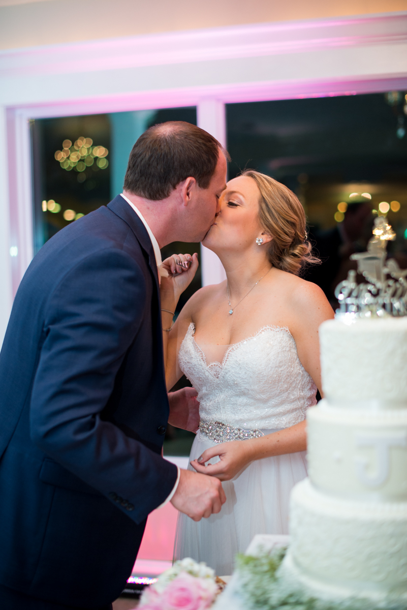 Elegant Navy and Blush Estate Wedding | Bride and Groom Cake Cutting Kiss