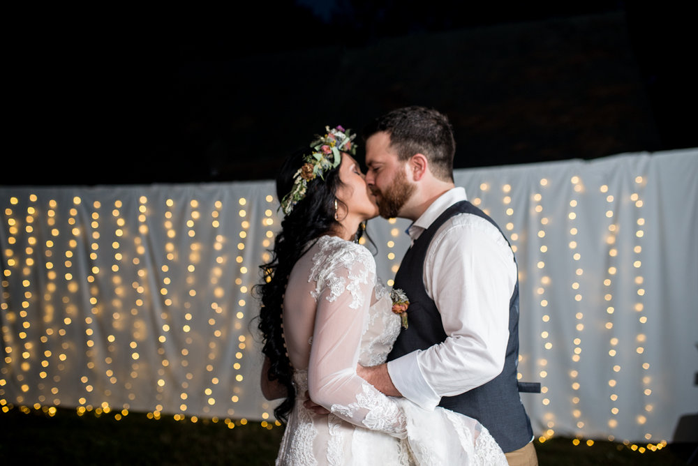 Intimate Boho Elopement | Bride and Groom First Dance in front of twinkling light wall