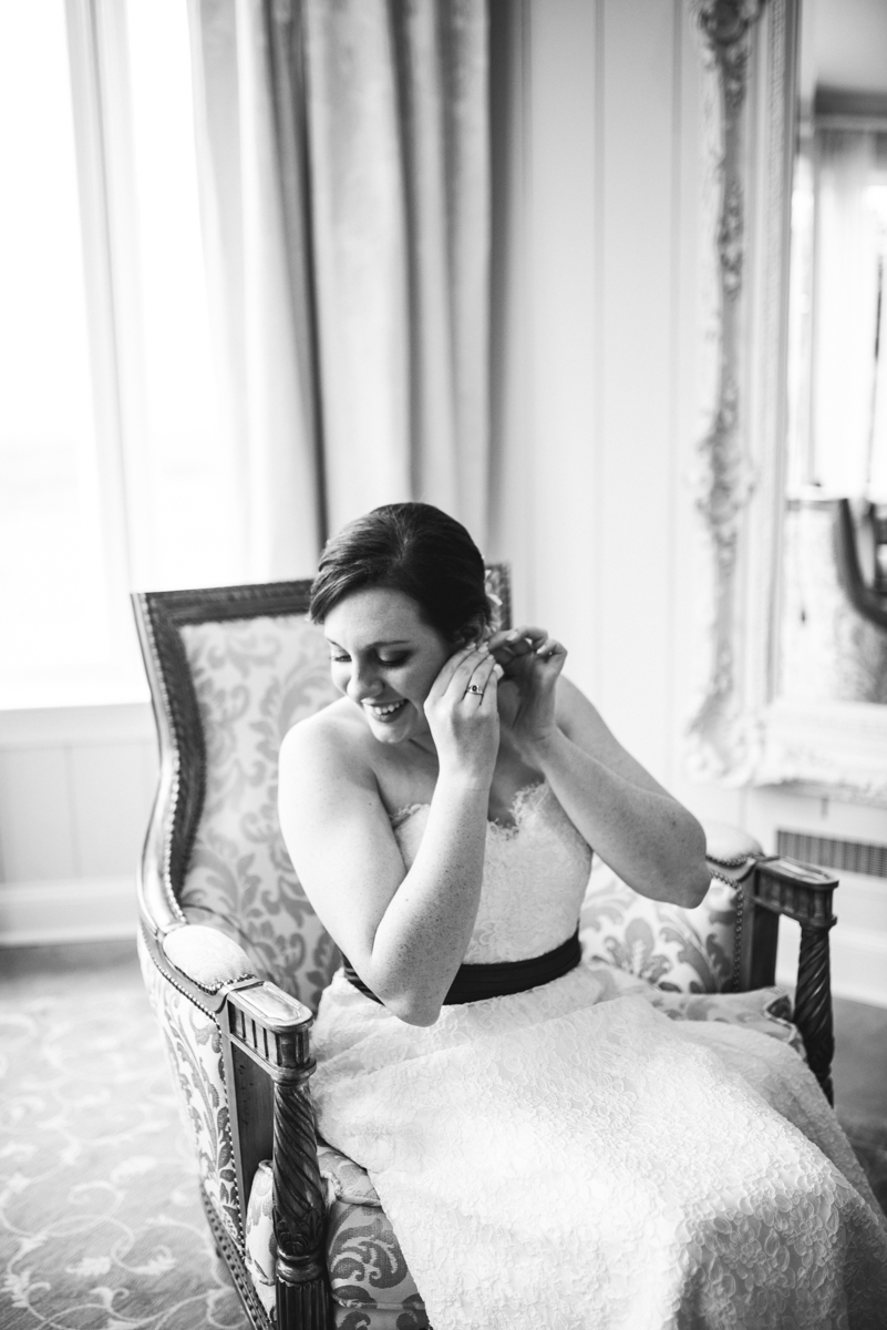 Gold and Burgundy Winter Winery Wedding | Iconic Bride putting on earrings