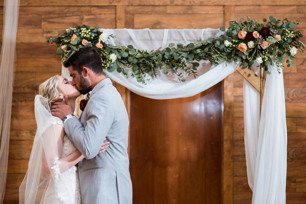 Burgundy + White Spring Wedding | Bride and groom kiss at altar