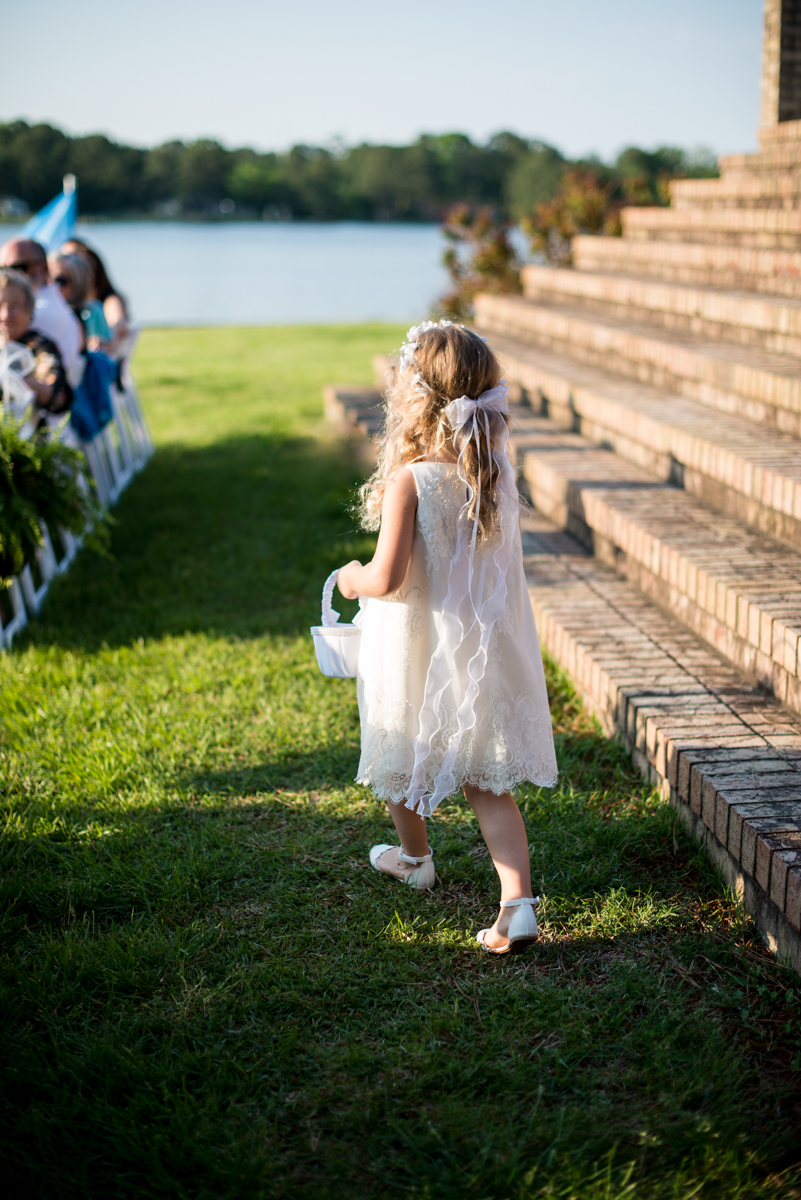 Intimate Backyard Summer Wedding on the Water | Flower girl walking down the aisle