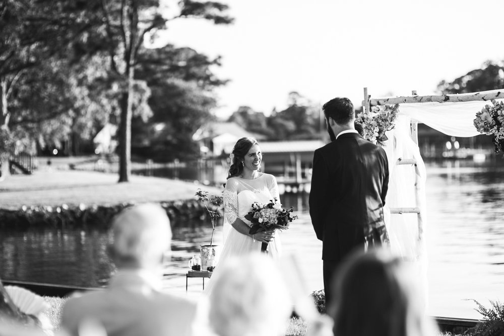 Intimate Backyard Summer Wedding on the Water | Bride and groom at altar