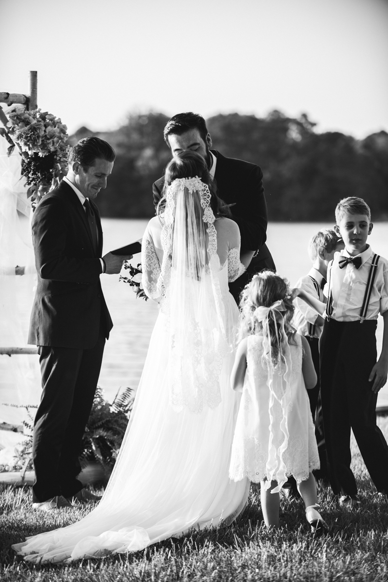 Intimate Backyard Summer Wedding on the Water | Bride and groom first kiss