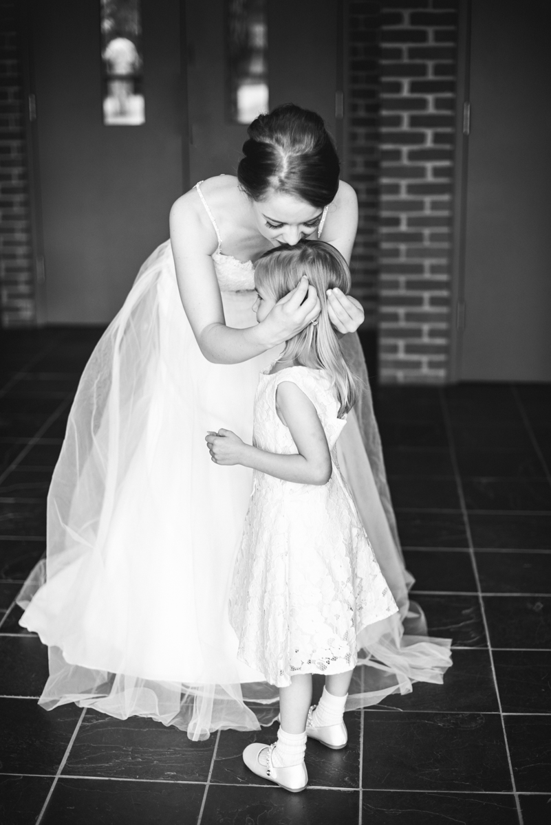 Yellow, Navy, and White Summer Wedding | Bride kissing the flower girl