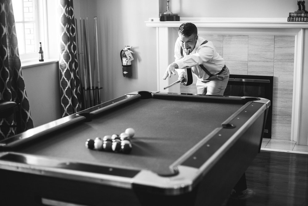 Minimalist White and Green Summer Wedding | Groom playing pool