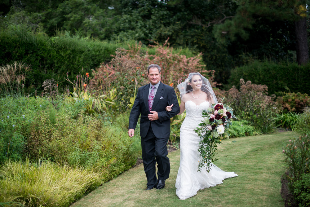 Blush and Burgundy Garden Wedding | Bride walking down the aisle outdoors