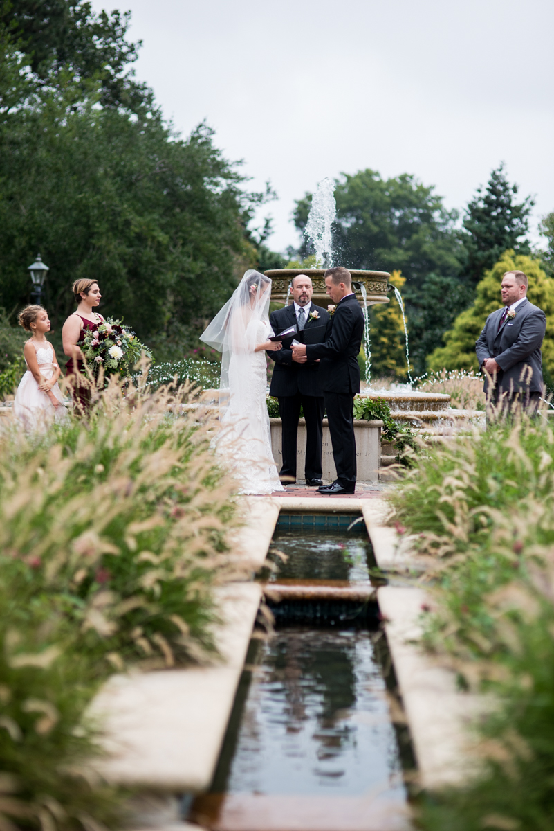 Blush and Burgundy Garden Wedding | Outdoor wedding ceremony by a fountain