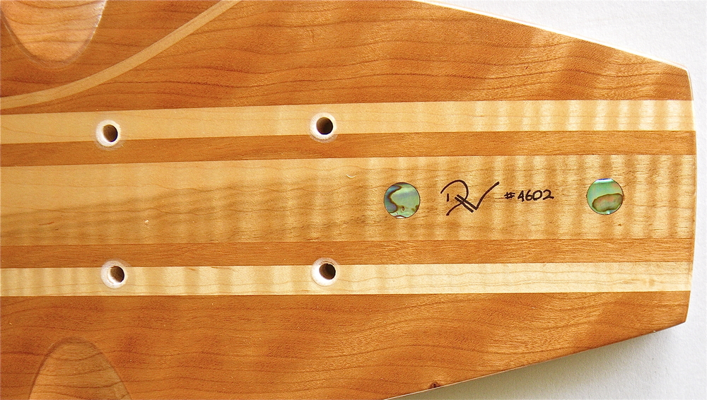 Detail shows Paua Shell inlay and signature/
