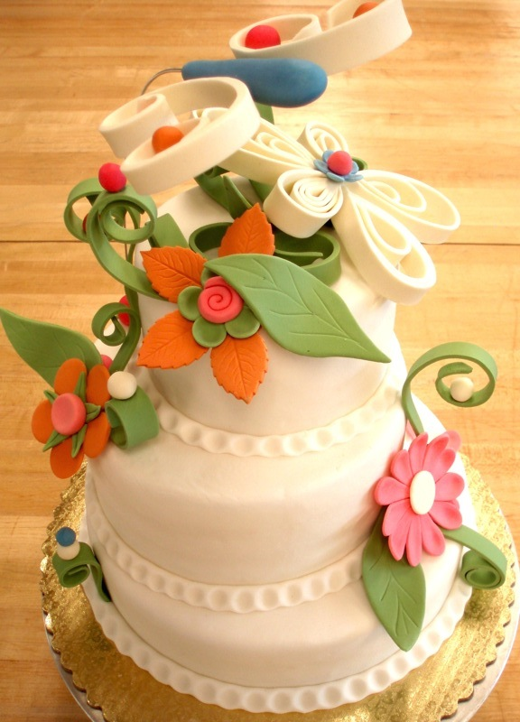 Vanilla sponge cake with whipped mascarpone and fresh strawberries; fondant finish, whimsical flowers