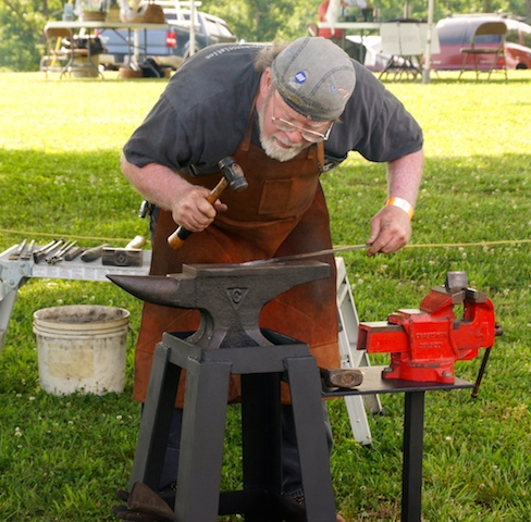 Doc Watson demonstrates his blacksmithing skills.