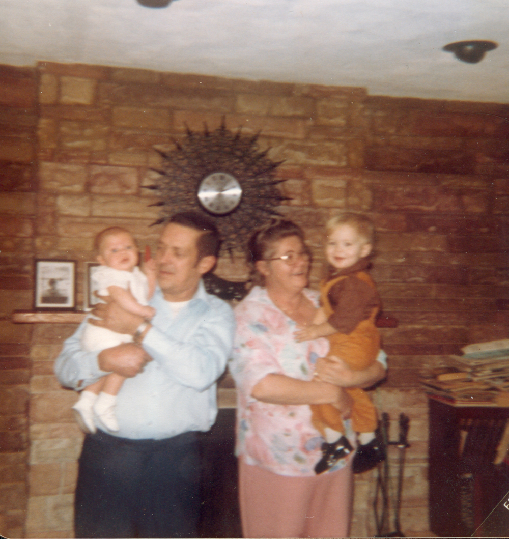 My maternal grandparents, John and Norma Tebo, holding me and my younger brother John