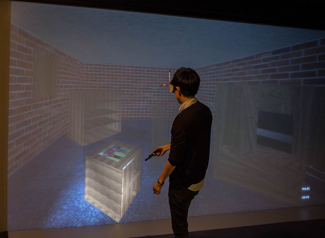 Using a virtual torch to send virtual light into simulated scene on the HIVE wall