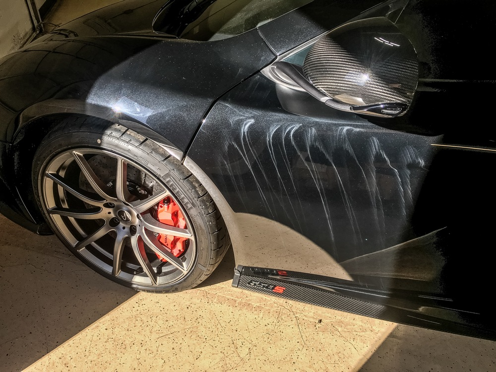 Brand New Mclaren 650S, 27 miles: Paint damaged due to improper buffing techniques by a sub-par detailer. The lines you see are known as 'holograms'