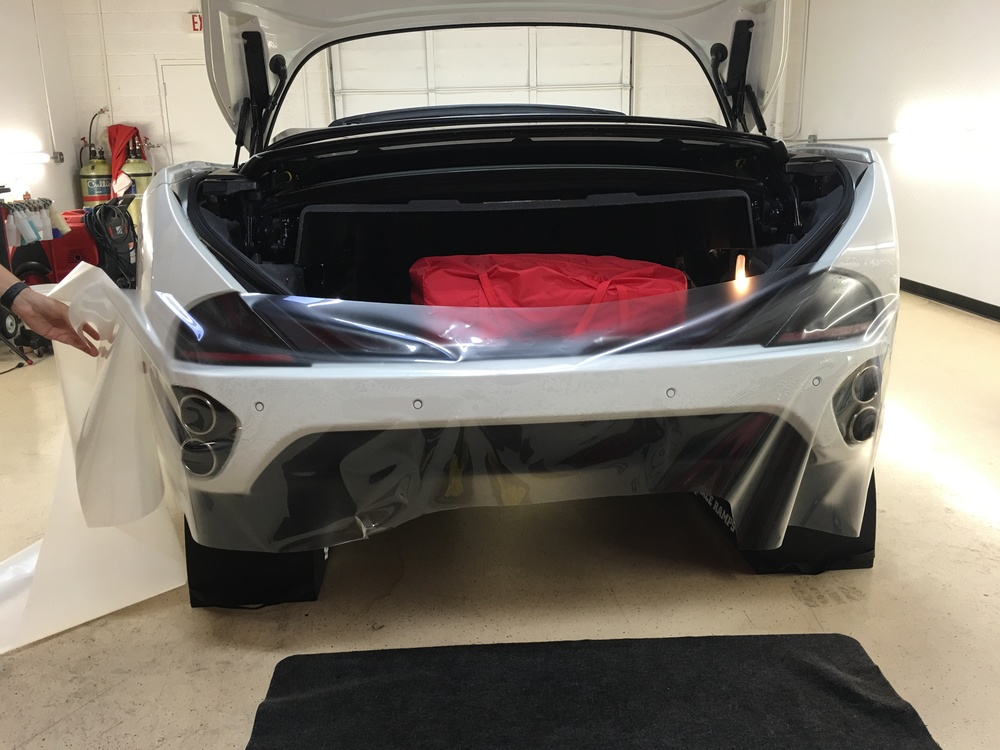 Our XPEL technician laying film out to custom-fit the rear bumper installation