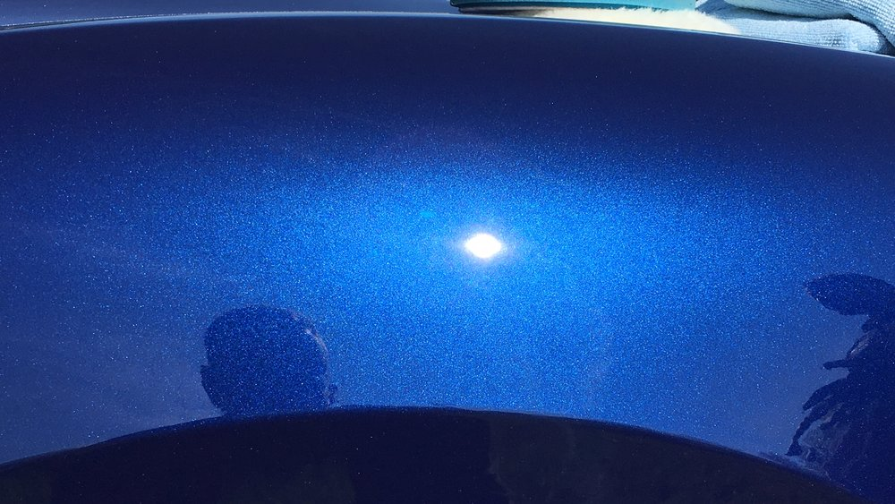 After paint correction, a hazeless, perfect sun can be seen in the reflection of the rear fender